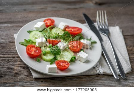 Appetizing greek salad with spices, cucumbers and feta cheese looking yummy, served with tableware