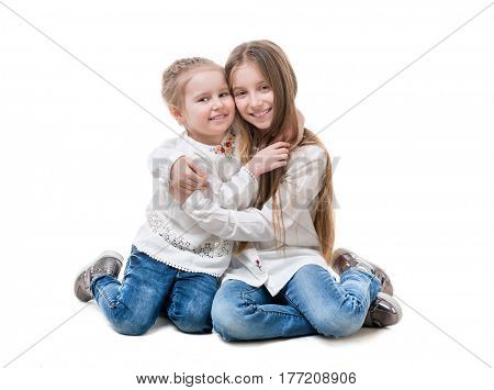 Siblings sitting, wearing similar clothes, silvery shirts, hugging each other, isolated on white background