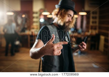 Brutal bearded coiffeur pose with scissors in hand