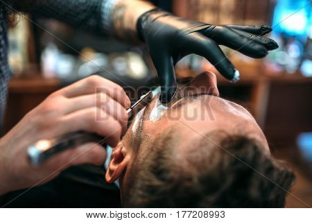Barber shaves the beard by straight razor
