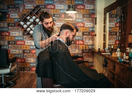 Barber makes hairstyle of client man by clipper