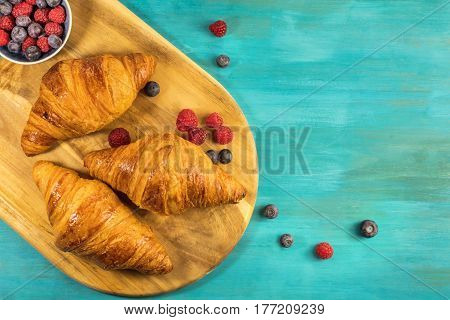 An overhead shot of crunchy French croissants with fresh raspberries and blueberries on a wooden cutting board and vibrant turquoise texture, with copy space