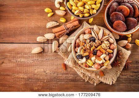 Mix of nuts and dried fruits on a old rustic table. Gold pistachios, cashews, hazelnuts, almonds. Food background with copyspace