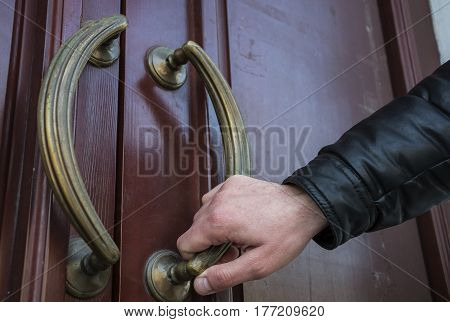 The man opens the door with a metal handle