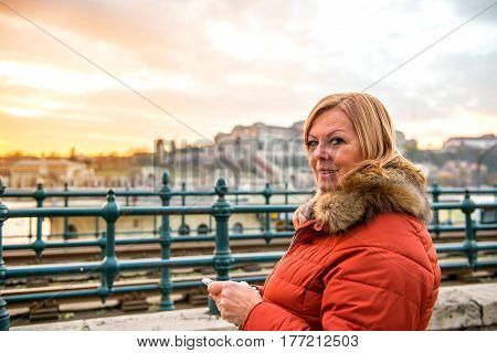 A nice middle age woman standing in the sunset in the city while using her phone