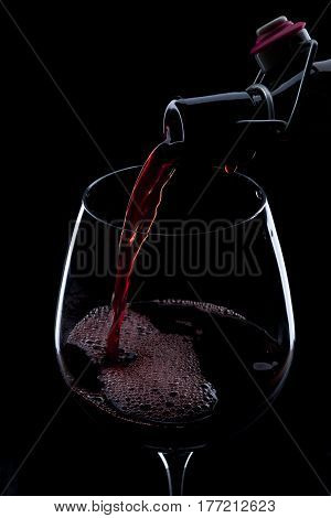 Pouring Red Wine From Bottle Into The Wineglass On Black Background.