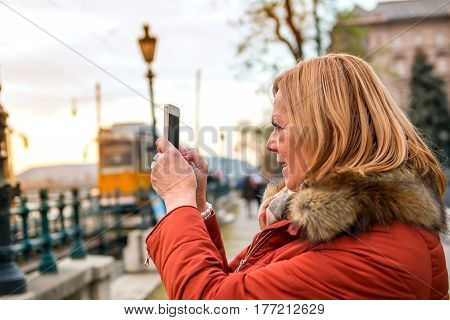 A nice middle age woman standing and taking photos of the sunset with her phone in the city