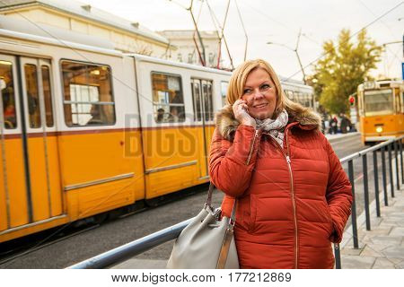 A nice middle age woman standing at a tram station in a winter jacket and speaking on her smartphone