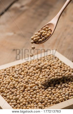 Soya beans in spoon on wooden table.