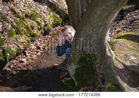 Small boy in the brook, kneels behind a tree and waves laughing forwards