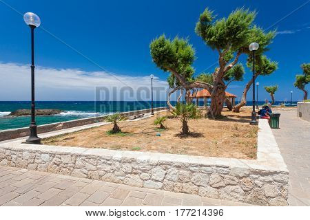 Chania Crete - 26 June 2016: Lamps trees and summer house are on the Embankment of Mediterranean Sea on the summer sunny day. Embankmentis located near the Old Town of Chania and it is favorite place for tourists who are visiting and walking there.