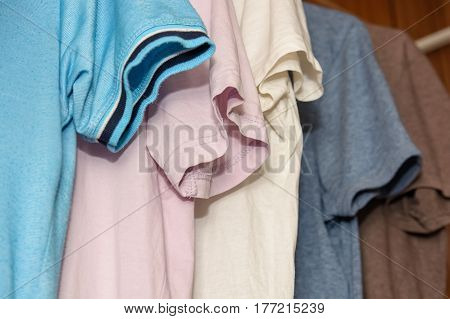 Close-up of colorful t-shirts on hangers in wardrobe