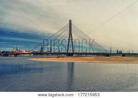 The capital of Latvia Riga in the spring with a view of the spires of cathedrals and churches on the background of the bridge on the Daugava river in Sunny day