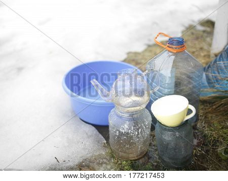Filling various bowls jars and kitchenware with springtime water falling from a building top