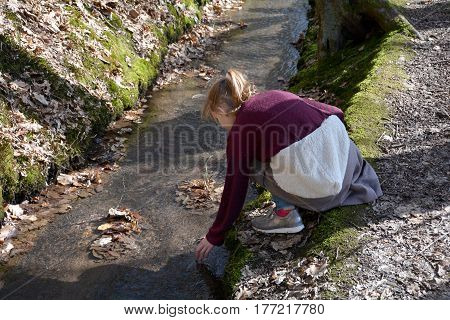 Young girl holds hand in the water of a brook in the wood