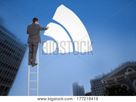 Digital composite of Businessman on a Ladder with white icon against a city landscape background