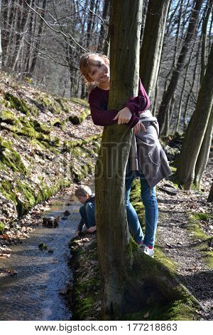 Girl holds on laughing in the tree, small boy plays behind in the brook