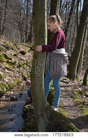 Girl in the tree looks in the brook, small boy plays behind in the water