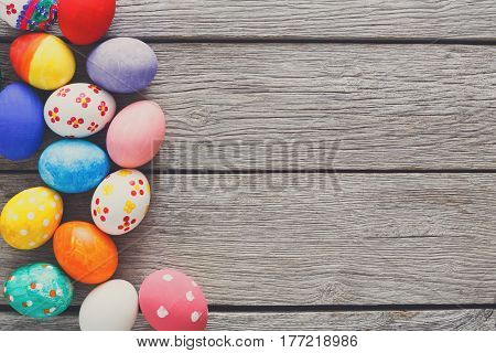 Easter eggs on wood background. Colorful handmade painted eggs on rustic table top view with copy space