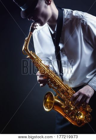 Young male performer playing saxophone on a dark background