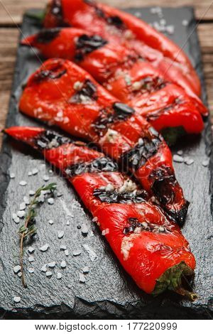 Appetizing and juicy grilled pepper served on black slate, close up view. Restaurant menu photo. Vegetarian cuisine, healthy lifestyle.