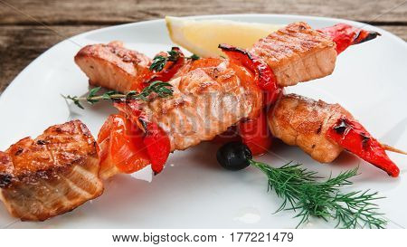 Appetizing salmon with tomatoes and chili pepper decorated with lemon on white plate, close up view. Japanese cuisine.