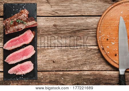 Delicious grilled beef steak sliced on black slate with professional knife on platter on rustic wooden table with copy space for text. American cuisine, kitchen, restaurant serving