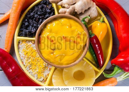Bowl of vegetable curry sauce and ingredients that go into making it - paprika chili pepper carrot pineapple gember. Used widely in Indian food.