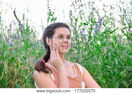 Russian girl dreams against the background of a wild flowers