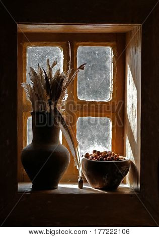 Antiquity scribe still life with goose pen in jar for write and dry ashberry in clay cup on wooden windowsill at dark hut.