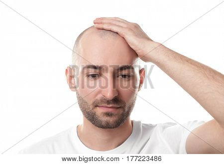Hair loss concept. Man touching his bald head on white background