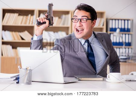 Funny businessman with gun in office