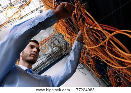 Handsome young engineer connecting cables in server room