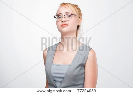 Young blonde woman looks shocked, stunned, taken aback and perplexed. Dumbfounded and bemused girl on grey background.
