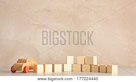 Cubes with space for text and wooden toy car on light background