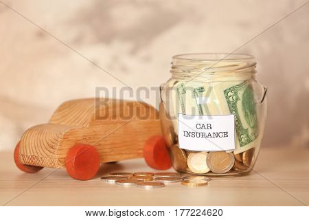 Glass jar with money and wooden car toy on table