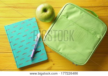 Lunch box, exercise book and appetizing green apple on yellow wooden background