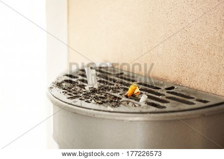 Trash bin with cigarettes butts, outdoor
