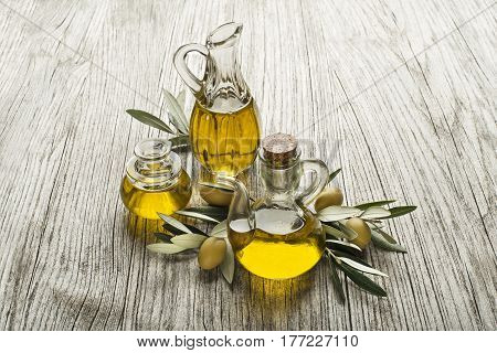 Olive oil in bottles with branch on the wooden background