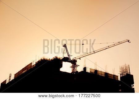 Silhouette - Building and construction crane and orange sky