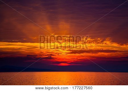 sun setting with rays in clouds over the Adriatic sea