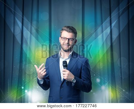 Businessman speaking into microphone with blue curtain behind him