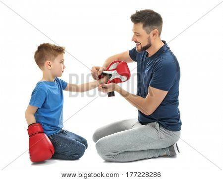 Handsome man helping his son to put on boxing gloves, against white background