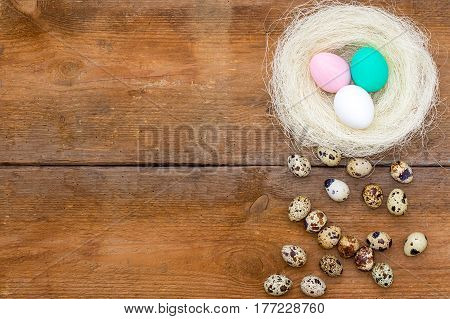 Nest With Colored Easter Eggs And Little Quail Eggs At The Old Brown Unpainted Wooden Background.