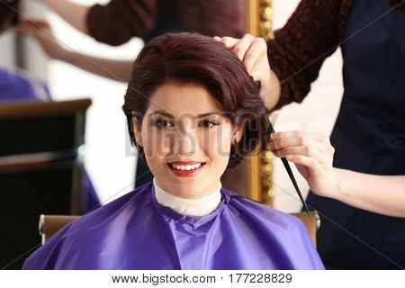 Hairdresser making beautiful haircut to young woman in beauty salon