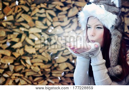 Young woman with long dyed red hair is wearing a fluffy hat with a wolf face and long pom poms is blowing magical snowflakes from her palms, posing on stacked logs background.