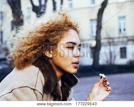 young pretty girl teenage outside smoking cigarette close up, looking like real junky, real social issues concept