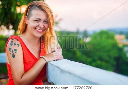 A lady in red laughs at the verandah of a summer restaurant. Beautiful happy girl with shaved temples in a red dress and with red lipstick.
