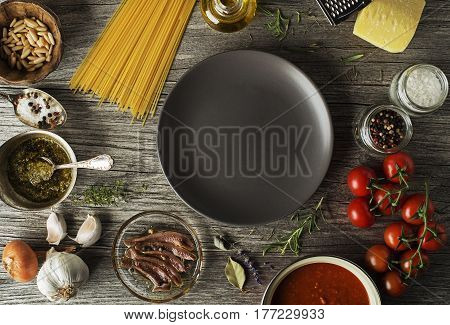Spaghetti with ingredients for cooking pasta on wooden background