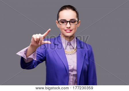 Businesswoman pressing virtual button on gray background